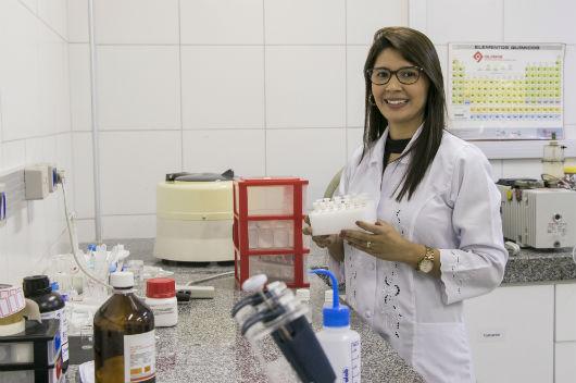 Pesquisadora Suely Alves na bancada do laboratório, segurando frascos com o estudo da liberação do medicamento (Foto: Viktor Braga/UFC)