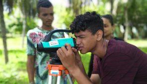Estudante olhando através de equipamento utilizado em medições topográficas (Foto: Luana Oliveira/PREX-UFC)