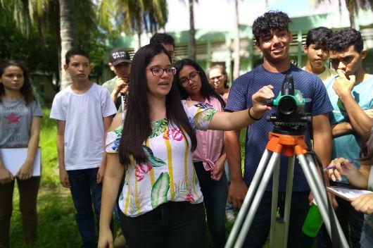 Estudantes em uma área externa do Campus do Pici recebendo instruções sobre equipamento utilizado nas medições topográficas (Foto: Luana Oliveira/PREX-UFC)