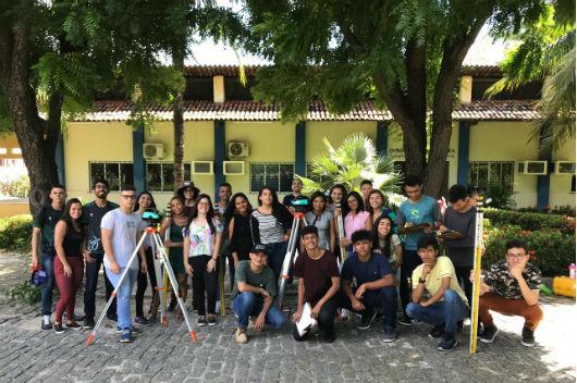 Cerca de 25 alunos do projeto posando para a foto, juntamente com alguns equipamentos utilizados durante as aulas na UFC (Foto: Luana Oliveira/PREX/UFC)