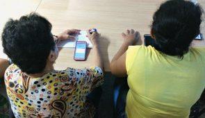 Duas mulheres de costas, com um celular sobre a mesa