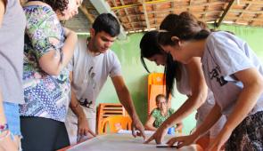 Estudantes analisando projeto em papel sobre a mesa, com moradora da comunidade aparecendo em segundo plano (Foto: Clarice Nascimento/PREX-UFC)