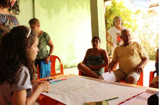 Estudantes desenvolvendo projetos e conversando com moradores, ao redor de uma mesa, na casa de uma moradora da comunidade (Foto: Clarice Nascimento/UFC)