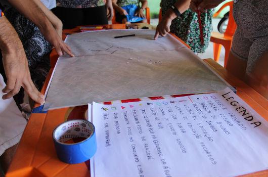 Pessoas em volta de uma mesa durante momento relativo ao processo de cartografia social (Foto: Clarice Nascimento/UFC)
