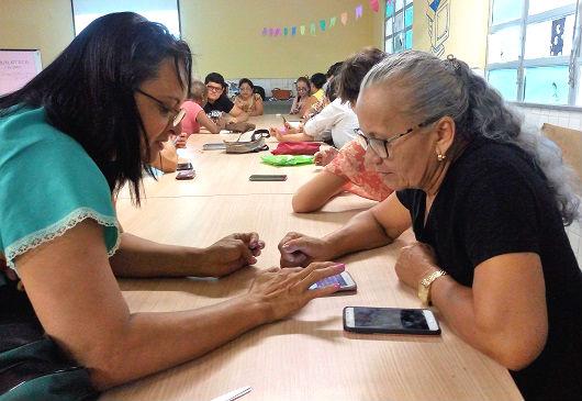 Mulher em frente a uma senhora, ensinando-a a usar o celular, posto sobre a mesa (Foto: Ely Eulle/UFC)
