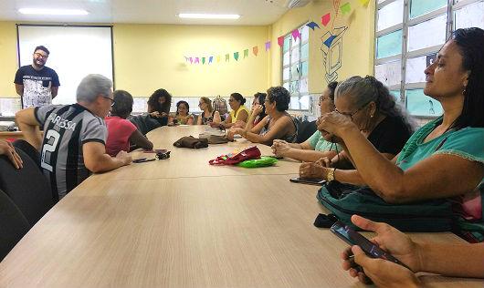 Pessoas sentadas à mesa, com um professor ao fundo (Foto:  Ely Eulle/UFC)