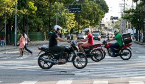 Cruzamento entre as avenidas Treze de Maio e da Universidade, com motociclistas em primeiro plano, pedestres atravessando, e outros veículos vindo ao fundo (Foto: Viktor Braga/UFC)