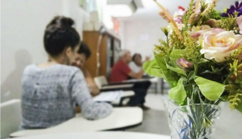 Em primeiro plano, jarro contendo um buquê de flores; em segundo plano, pessoas conversando em cadeiras (Foto: Luana Oliveira/PREX-UFC)