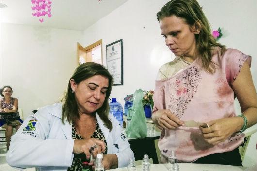 Enfermeira sentada desenvolvendo atividades com frascos em uma mesa, ao lado de uma mulher que está em pé acompanhando o momento (Foto: Luana Oliveira/PREX-UFC)