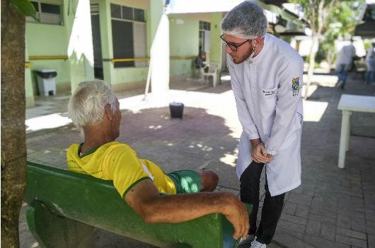 Pessoa em pé, usando jaleco, conversando com idoso que está sentado em um banco (Foto: Luana Oliveira/PREX-UFC)