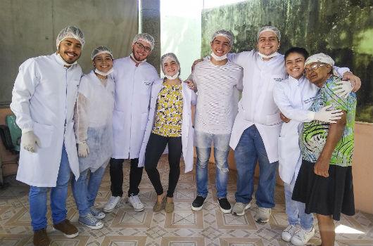 Grupo de sete integrantes do projeto, abraçados e sorrindo, posando para a foto ao lado de uma das idosas atendidas (Foto: Luana Oliveira/PREX-UFC)