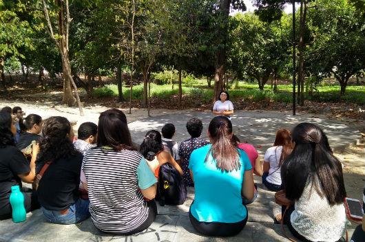 Pessoas sentadas no anfiteatro do parque, acompanhando a explicação da coordenadora do projeto (Foto: Luana Oliveira/PREX-UFC)