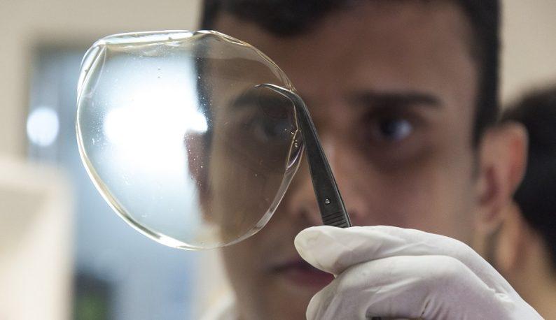 Pesquisador segurando um filme transparente circular com uma pinça (Foto: Viktor Braga/UFC)