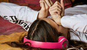 Jovem, com fone de ouvido rosa, deitada esfregando os olhos de sono (Foto: Luisella Planeta Leoni por Pixabay)