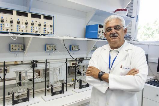 O Prof. Aldo Lima em pé, de braços cruzados, em um laboratório de pesquisa (Foto: Viktor Braga/UFC)