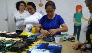 Mulheres manuseando retalhos em uma mesa (Foto: Luana Oliveira/PREX-UFC)