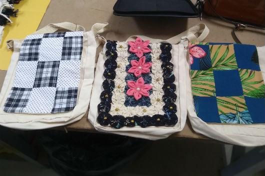 Três bolsas produzidas com retalho expostas sobre uma mesa (Foto: Luana Oliveira/PREX-UFC)