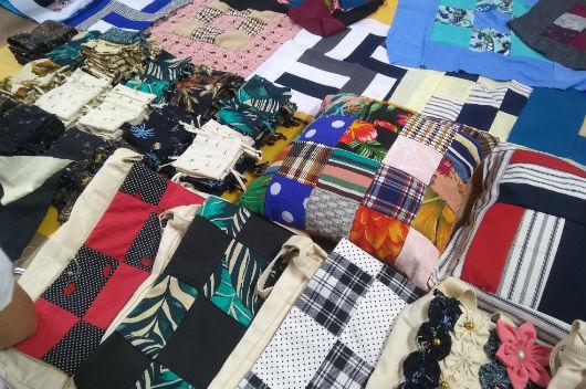 Almofadas, bolsas e outros produtos produzidos no curso, expostos sobre uma mesa (Foto: Luana Oliveira/PREX-UFC)