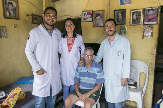 Equipe de 3 fisioterapeutas em pé e paciente sentado (Foto: Viktor Braga/UFC)