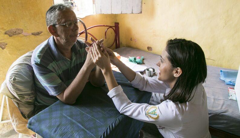 Paciente sentado e com as mãos cruzadas recebendo o acompanhamento de estudante de fisioterapia (Foto: Viktor Braga/UFC)