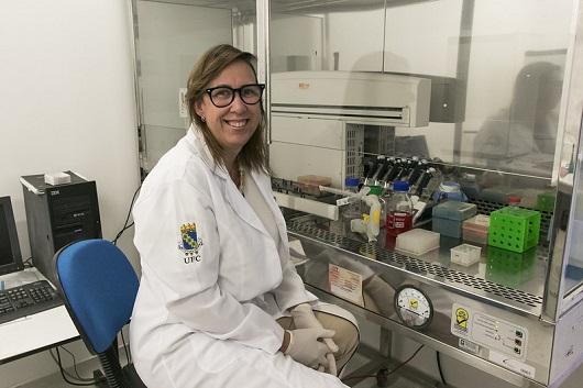 A professora Cláudia do Ó Pessoa sentada em uma bancada do laboratório