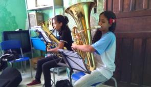 Duas estudantes crianças tocando instrumentos de sopro