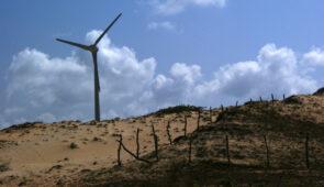 Região de dunas, com uma hélice de energia eólica ao fundo