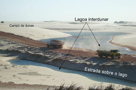 Imagem panorâmica de campo de dunas e de lagoa interdunar, sendo cobertas pela construção de uma via de acesso