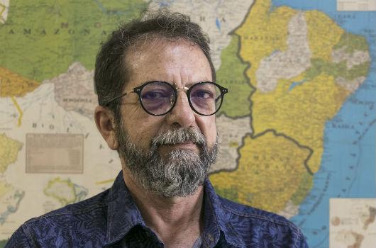 Prof. Jeovah Meireles, posando para foto na frente de um mapa