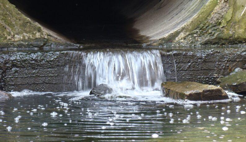 Saída de esgoto, com água sendo despejada