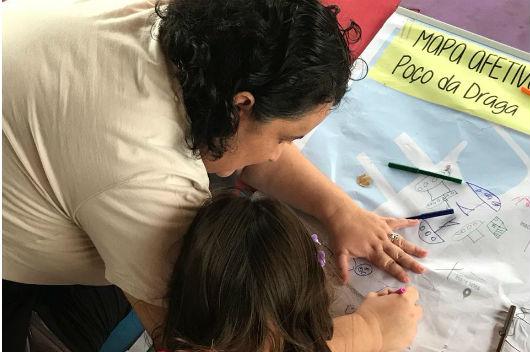 Pesquisadora e criança desenhando no mapa da cidade Foto: Arquivo pessoal/ Grupo Rastros Urbanos)