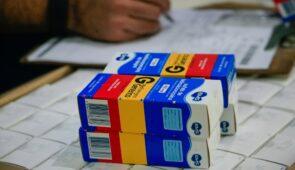 Em primeiro plano, caixas de sulfato de hidroxicloroquina sobre uma caixa; em segundo plano, há a mão de uma pessoa fazendo anotações em uma prancheta (Foto: Jader Paes/Agência Pará)