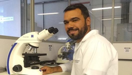 Fotografia do pesquisador em laboratório à frente de um microscópio