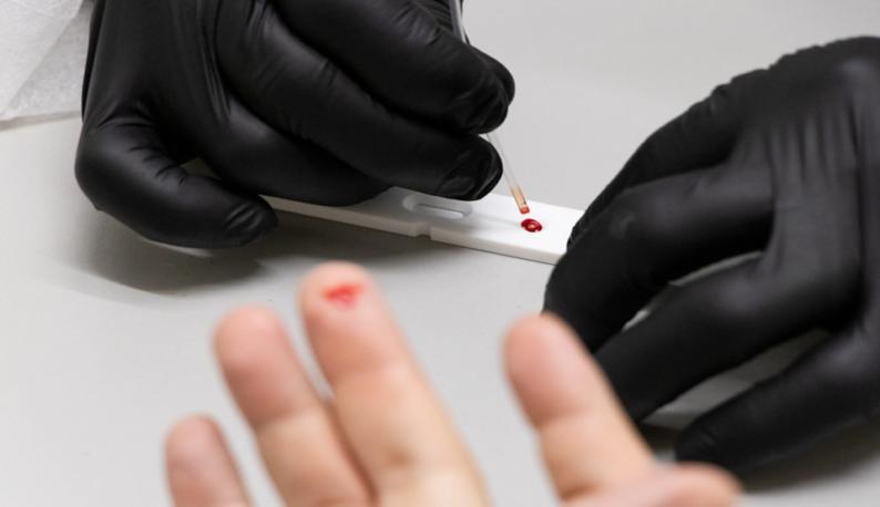 Dedo furado e sangue sendo usado em equipamento de testagem