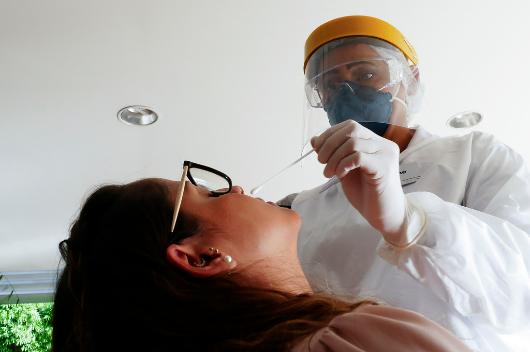 Agente de saúde utiliza cotonete no nariz de uma mulher para testagem de covid-19