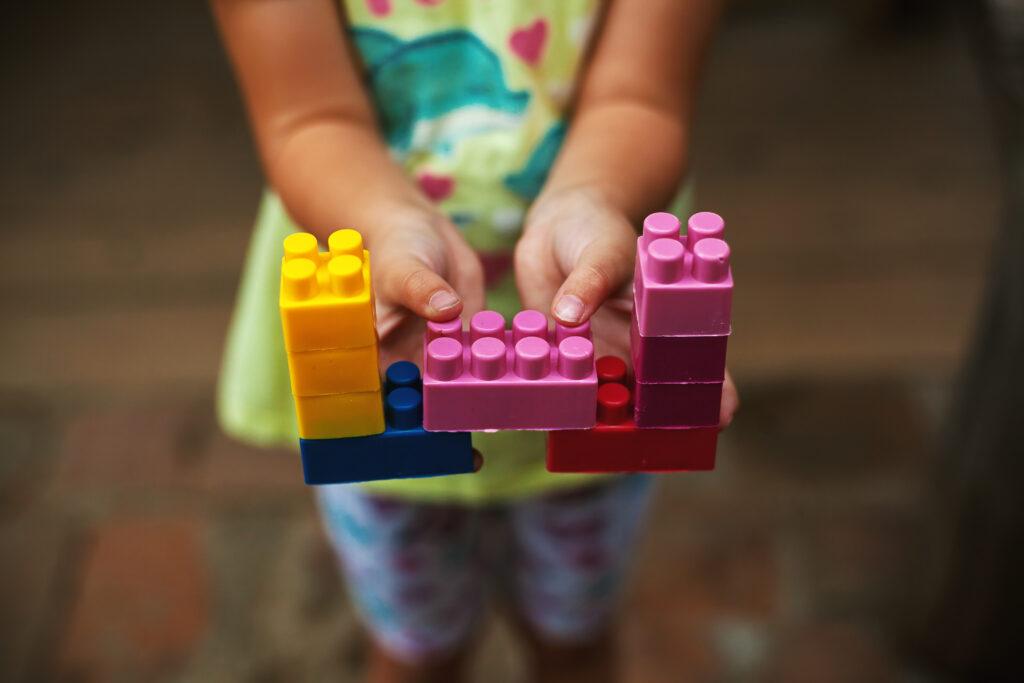 Mãos de menina segurando blocos de montar