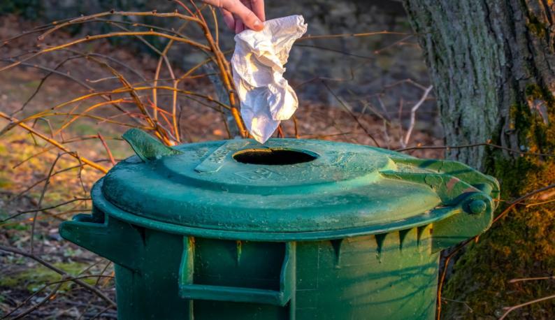 Papel sendo jogado em cesto de lixo