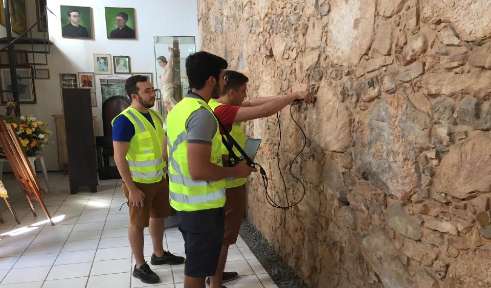 Pessoas utilizam equipamentos em parede de prédio histórico para análise