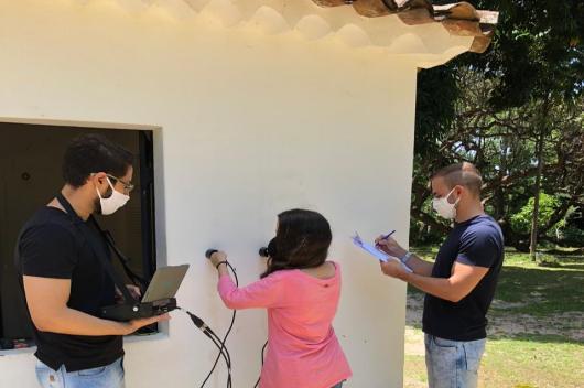 Três pesquisadores avaliam a fachada de uma construção histórica