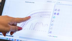 Dedo apontando para gráfico representando aumento na tela do computador