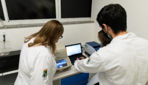 Três pesquisadores olhando para notebook na bancada do laboratório